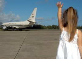 girl in a white dress waving goodbye to the plane