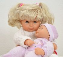 cute doll with white hair holds baby doll