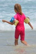 Rear view of a child in a pink bathing suit near the water