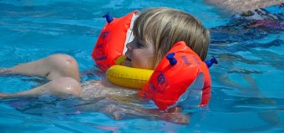 blond child girl in swim ring on water