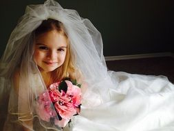 Child dressed up in the wedding dress