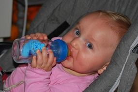 baby drinks from a bottle
