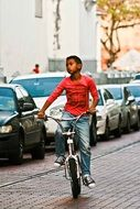 dark skin child boy riding bicycle on street along cars in row