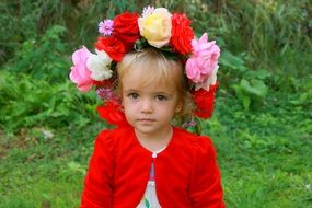 little blond girl with a wreath of large flowers on her head