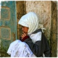 sad child girl sits at wall, morocco