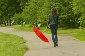 girl in black clothes walking with red umbrella in park