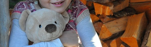 child with teddy bear soft toy
