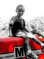child on a tractor in black and white background