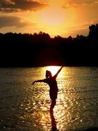 girl` silhouette sunset water