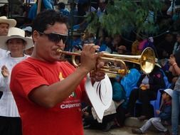 mature man plays trumpet on carnival, peru, cajamarca