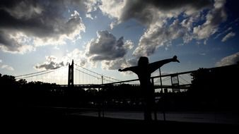 silhouette of girl in front of bridge at cloudy sky