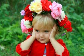 Beauty of thw little girl with a wreath of roses on her head