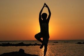 silhouette of a man in a yoga pose at sunset