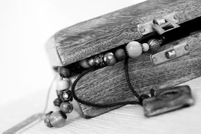 black and white photo of a wooden casket with bracelets