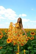 girl in a dress on a background of a field of sunflowers