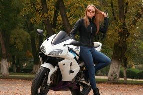 beautiful girl in a leather jacket leaned on the motorcycle