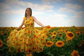 Girl in a lush yellow dress against the backdrop of a field of sunflowers