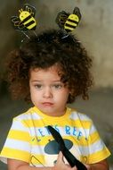 funny horns in the form of bees on the head of a blue-eyed child with curly hair