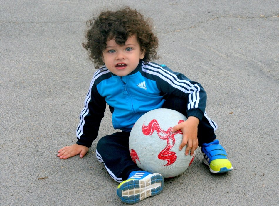 A child with curly hair with a ball sits on the asphalt