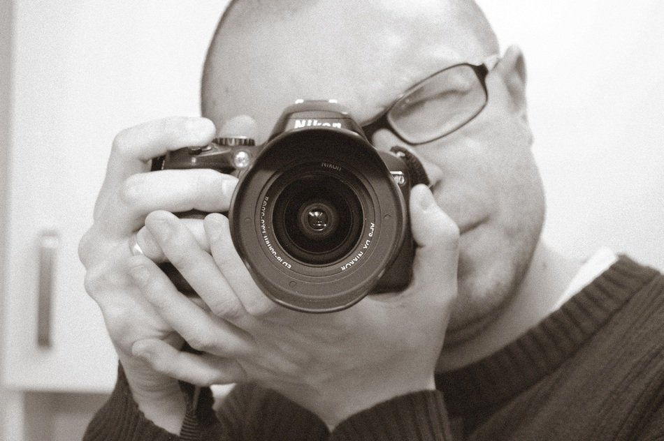 Black and white image of a photographer with a camera in his hands