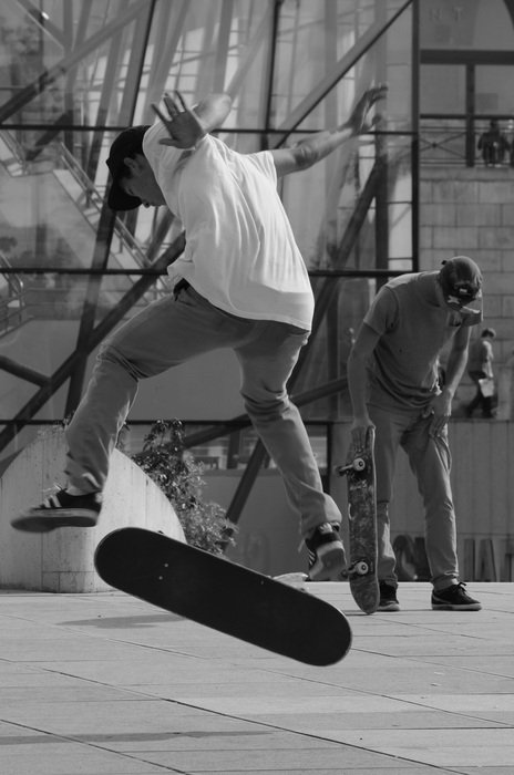 Black and white image of people on a skateboard