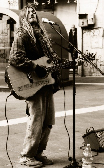 Black and white image of a street musician with a guitar and a microphone