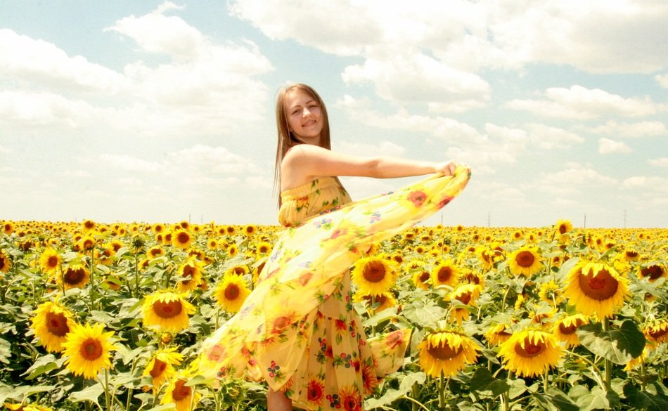 Girl in a beautiful dress among sunflowers