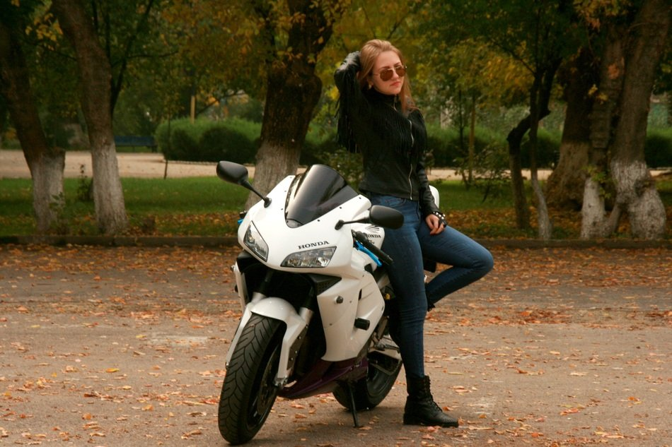 girl with blond hair in a leather jacket leaned on the bike