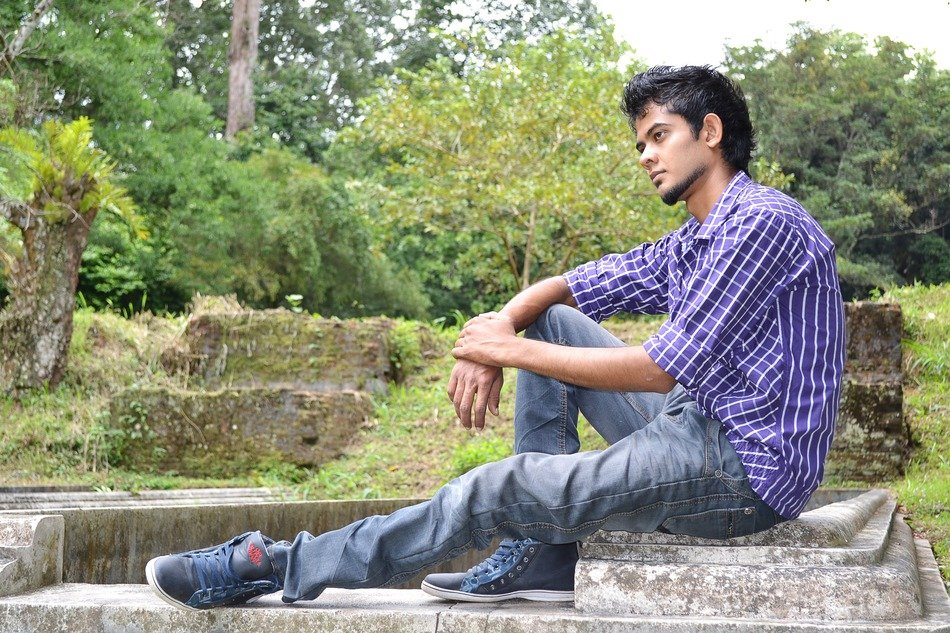 Lonely handsome young man sitting on stones in Ceylon
