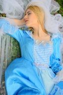 Sleeping blonde princess in a blue dress in the spring