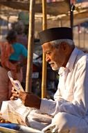 indian old man reading newspaper