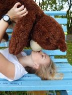 girl kissing a toy bear