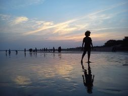 silhouette of a boy on the evening beach