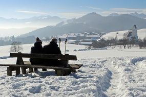 couple resting on a bench against the background of a winter landscape