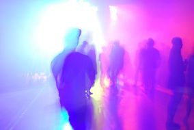 colored silhouettes of people dancing in a disco in a nightclub