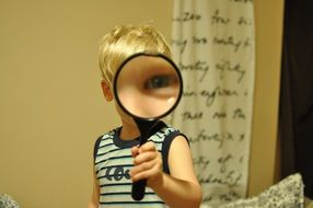 child play with magnifying glass