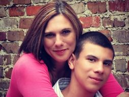 portrait of mother and son near a brick wall