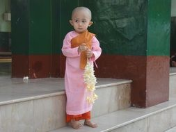 diffident child in a pink robe of monk professes Buddhism, Myanmar (also known as Burma)
