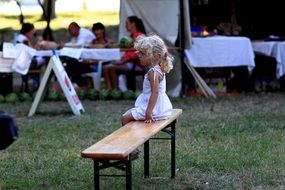 little girl sits on bench