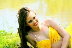 portrait of a beautiful woman in a yellow suit on a background of a nature