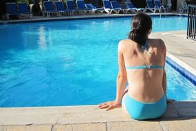 girl in a blue bathing suit near the pool