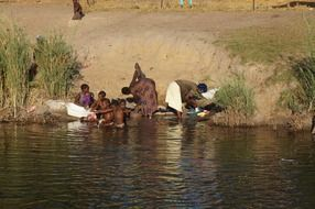 african family wash clothes in the river
