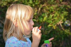 child girl blowing bubbles
