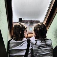 two sisters look out the window in rainy weather