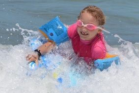 little girl is surfing in waves