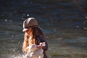 pretty girl long hair in hat water view