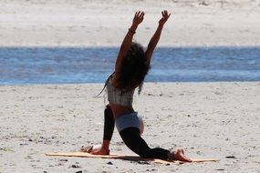 Girl on the beach practicing yoga