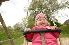 cheerful girl swinging on a swing