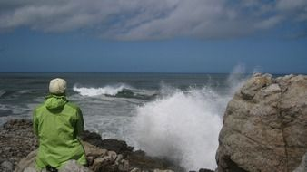 person in rain jacket sitting on rock at stormy sea, south africa