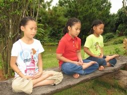 three children in the lotus position